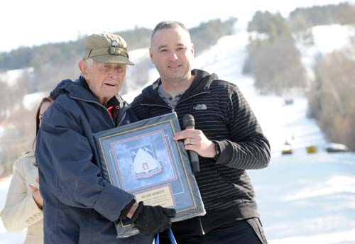 Sergeant Major Gonzolo Lassally of the 10th Mountain Division presents a regimental memento to Nelson Bennett.