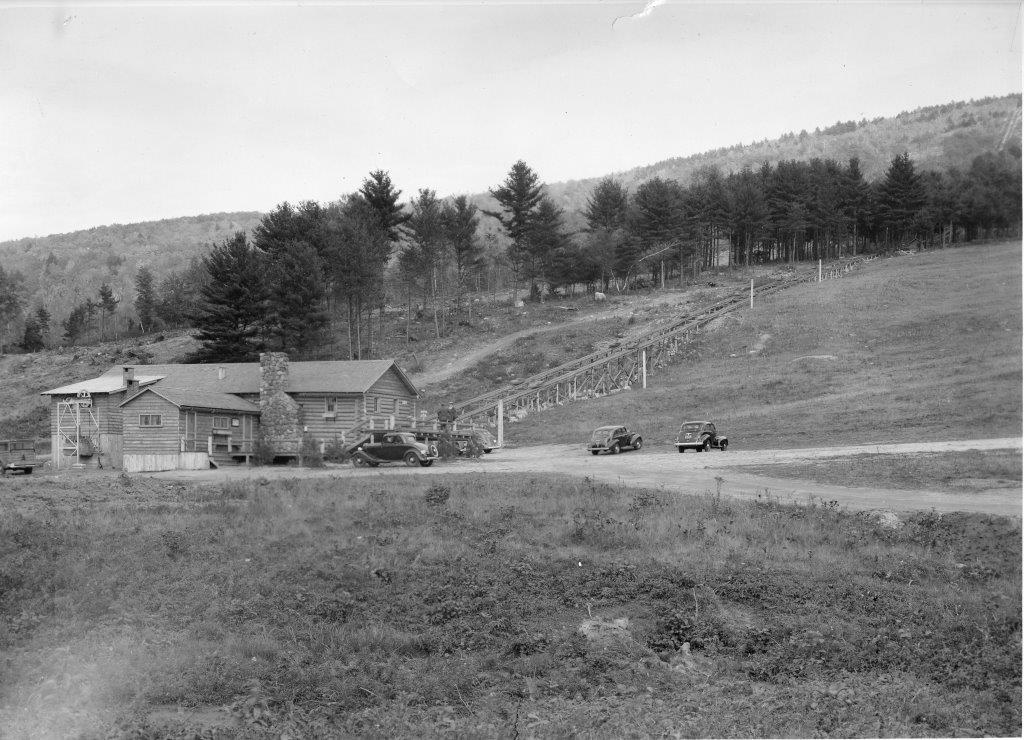 The newly-cut North Slope can be seen behind the base lodge in this photograph of Cranmore. The log walls of part of this building can still be seen in the main base lodge at Cranmore today.  Courtesy of North Conway Public Library